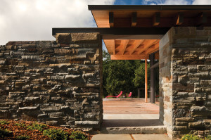 The wall cladding, composed of a unique type of Bluestone known as Llenroc stone, was used extensively for the exterior and interior of the home. Thousands of these stones were placed by hand to create the massive wall that frames the entire house and backyard, which relays a rugged texture since the stones are sporadically placed. Photo ©Nic Lehoux Architectural Photography.