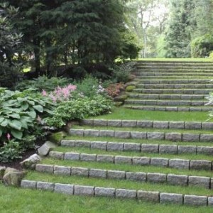 Curving grass steps add an elegant accent to a sloping garden. Belgian Block act as the step risers. Design and installation by Jan Johnsen, Johnsen Landscapes & Pools.