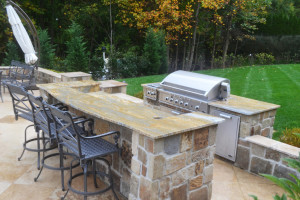 An outdoor kitchen built of natural stone with granite countertops is the perfect addition to finish an outdoor entertaining space. Photo courtesy of RTK Design Group.