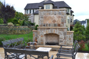 This outdoor fireplace was built of natural stone, decorated with a travertine mosaic inlay to create a one-of-a-kind look. Photo courtesy of RTK Design Group.